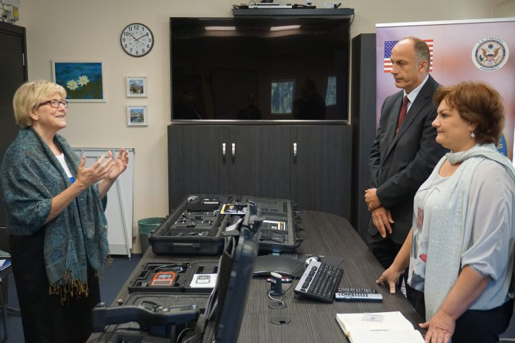 Two women, including Ambassador Uyehara and a man standing around a table with equipment on top of it