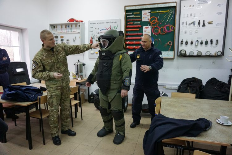 Three soldiers in a room, one wearing full protective equipment