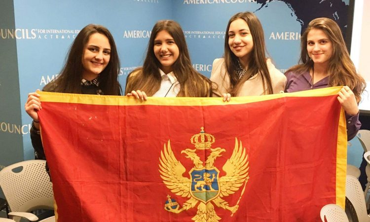 Four girl students holding Montenegrin flag