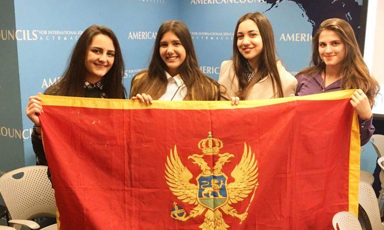 Four girl students holding Montenegrin flag