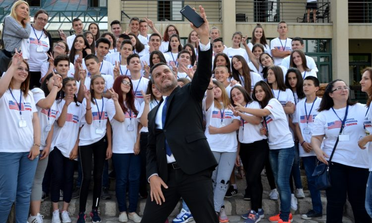 A man takes a selfie with a group of students in the background