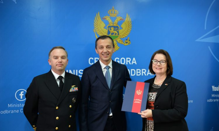 Ambassador Judy Reinke and Minister of Defense Predrag Boskovic signing an agreement
