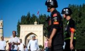 Chinese police patrol as Muslims leave a mosque in Kashgar