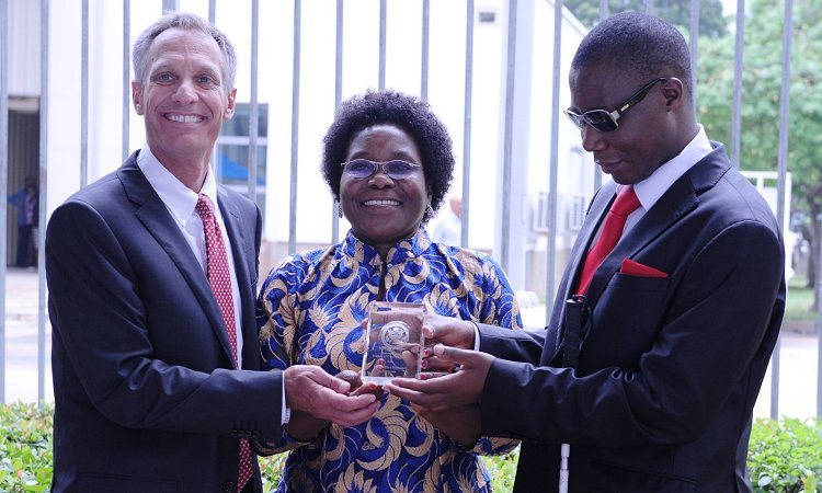 U.S. Ambassador Mark B. Childress, Deputy Permanent Secretary Amon Mpanju from the Ministry of Constitutional and Legal Affairs, and the Executive Director of Under the Same Sun Tanzania, Vicky Ntetema, hold the 2016 International Women of Courage award.