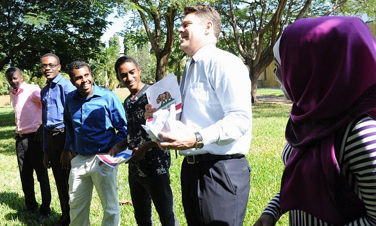 Tanzanian secondary school students who recently returned from a year-long academic exchange in the United States share a light moment with U.S. Embassy Regional English Language Officer Scott Chiverton.