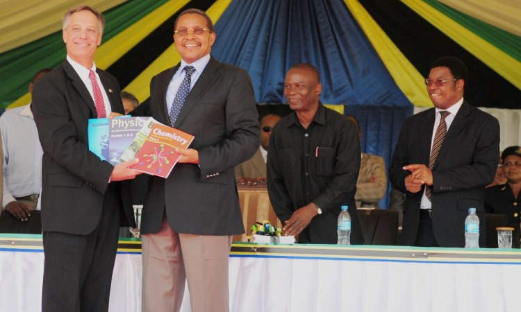 U.S. Ambassador Mark Childress and President Jakaya Kikwete pose with science textbooks donated by the U.S. Government