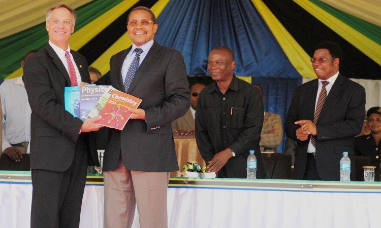 U.S. Ambassador Mark Childress and President Jakaya Kikwete pose with science textbooks donated by the U.S. Government