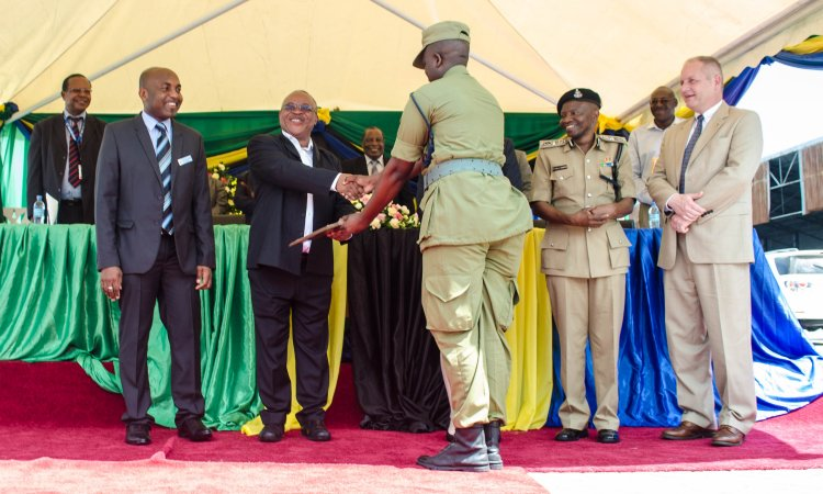 Minister of Natural Resources and Tourism Hon. Professor Jumanne Maghembe awards a certificate to a Tanzanian Police officer upon the completion of a canine detection training program from U.S. Customs and Border Patrol (CBP).