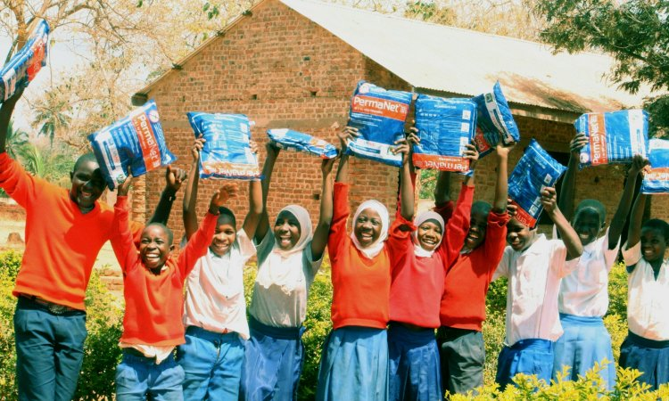 Tanzanian children in the Ruvuma Region hold up new bed nets from the U.S. Government's Presidential Malaria Initiative (PMI).
