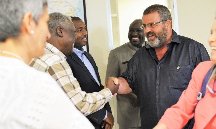 USAID Mission Director Andy Karas (right) congratulates Media and Communication Director of InterNews Wenceslaus Mushi after the launching of a civil society and media strengthening Boresha Habari project in Dar es Salaam yesterday.