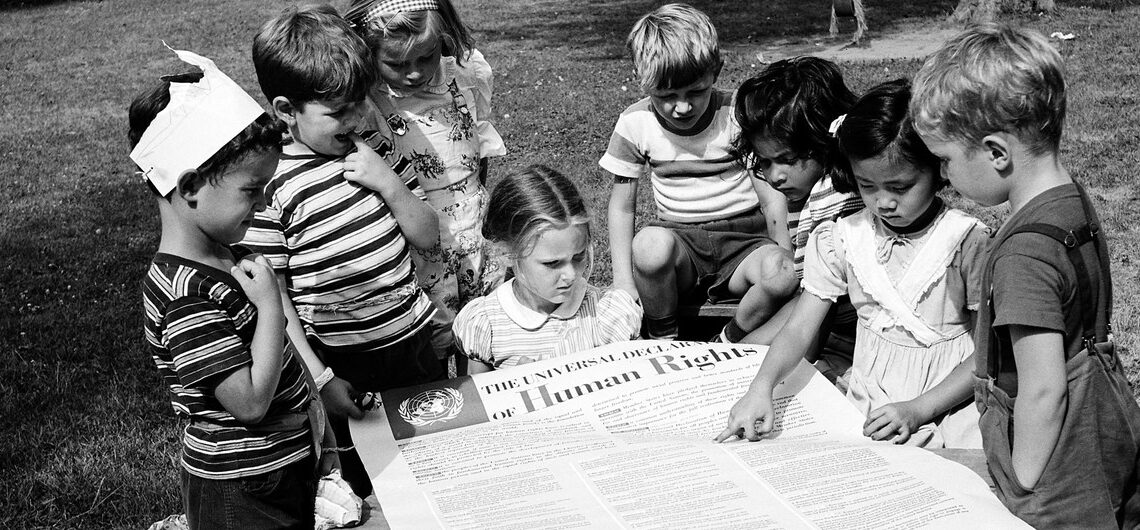 Children at the United Nations International Nursery School look at a poster of the Universal Declaration of Human Rights. (© Universal History Archive/Getty Images)