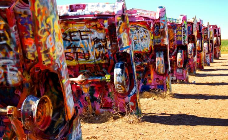 Cadillacs antiguos decorados con pintura en aerosol y enterrados en el suelo de Cadillac Ranch, una colorida atracción al borde de la carretera en Amarillo, Texas. © lumierefl/Flickr