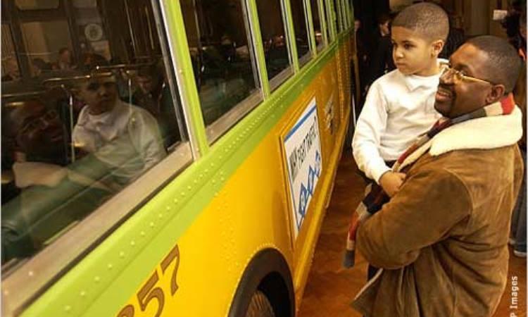 Un hombre y su hijo observan el autobús en el que Rosa Parks se rehusó a ceder su asiento en 1955, un momento crucial en el movimiento por los derechos civiles. (AP Image)