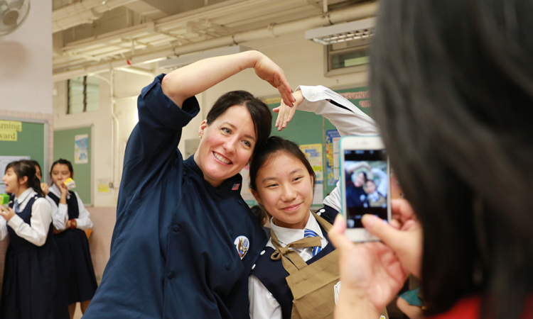 Chef Pomeroy takes a photo with a student (State Dept.)