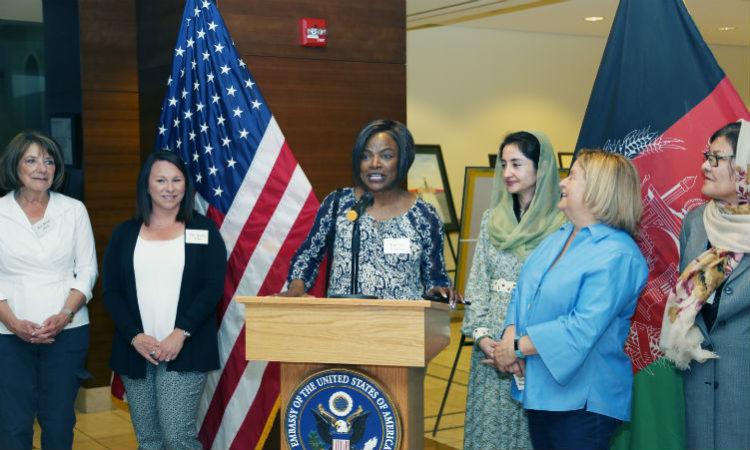 Women standing around podium. (Embassy Image)