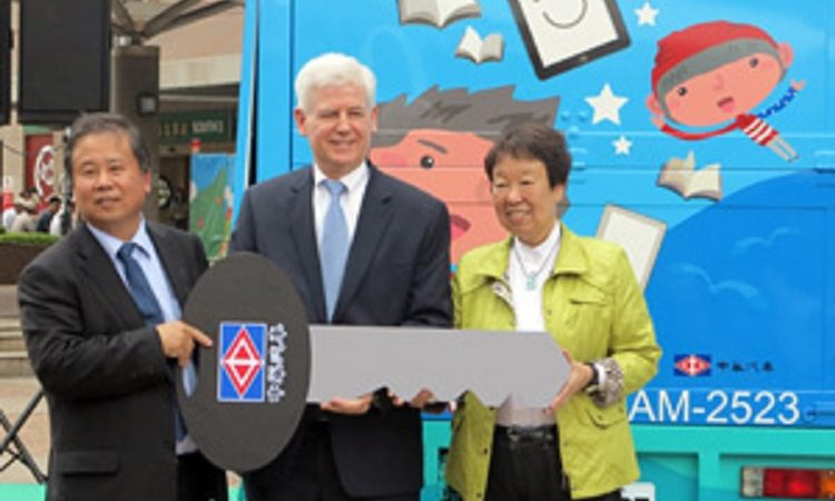 AIT Director Christopher J. Marut (center), China Motor General Manager Hsing-tai Liu (left), and CommonWealth Foundation Chairwoman Diane Ying, pose with a ceremonial key at AIT's new Mobile American Corner on April 30, 2013 at the Taipei Main Stat (Photo: AIT)