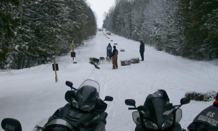 Snowmobilers watch the annual dog sled race on Drummond Island. (Credit: CBP)