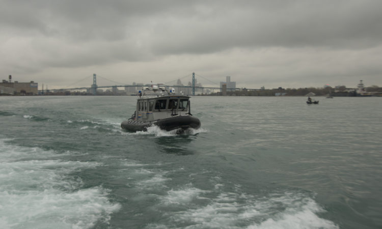 The crew of a Royal Canadian Mounted Police boat patrols the Detroit River just south of the Ambassador Bridge and the skylines of downtown Detroit and Windsor, Ontario, while carrying a U.S. Coast Guard law enforcement officer during a Shiprider patrol demonstration April 30, 2015. Shiprider is a program that enables specially-trained officials, from both Canada and the United States, to pursue or interdict suspected criminals transiting across the shared maritime border. U.S. Coast Guard photo by Petty Officer 2nd Class Levi Read