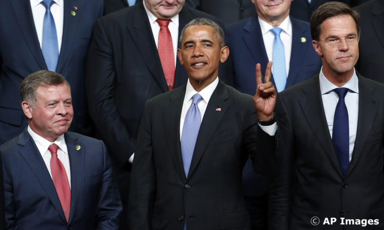 President Barack Obama, flanked by Jordan's King Al Sharif Abdullah Bin Al Hussein, left, and Dutch Prime Minister Mark Rutte, gestures as they wait for two more leaders prior to posing for a group photo during the Nuclear Security Summit, Friday, April 1, 2016, in Washington. (AP Photo/Alex Brandon)