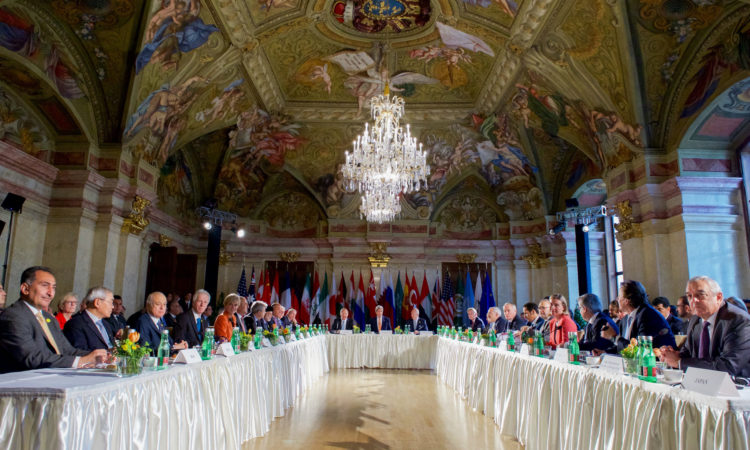 U.S. Secretary of State John Kerry sits between Russian Foreign Minister Sergey Lavrov and United Nations Special Envoy for Syria Staffan de Mistura on May 17, 2016, at the Palais Niederosterreich Hotel in Vienna, Austria, at the outset of a meeting of the International Syria Support Group. [State Department photo/ Public Domain]