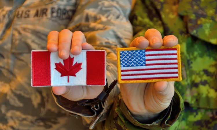 Participants in Exercise VIGILANT SHIELD 17 in Yellowknife show off the US & Canada flags. Credit NORAD.