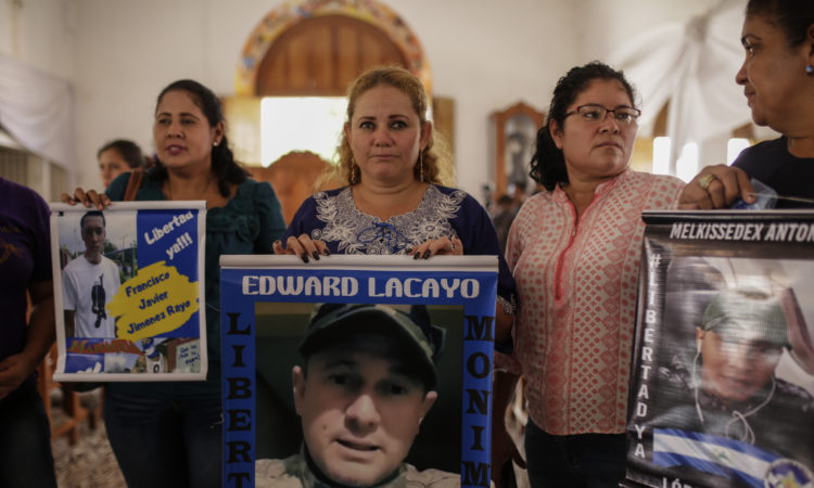 Mothers and relatives of jailed anti-government demonstrators holds signs with images of their imprisoned sons and family, at the San Miguel Arcangel Church in Masaya, Nicaragua, Thursday, Nov. 14, 2019. The group started a hunger strike to demand their freedom. (AP Photo/Alfredo Zuniga)