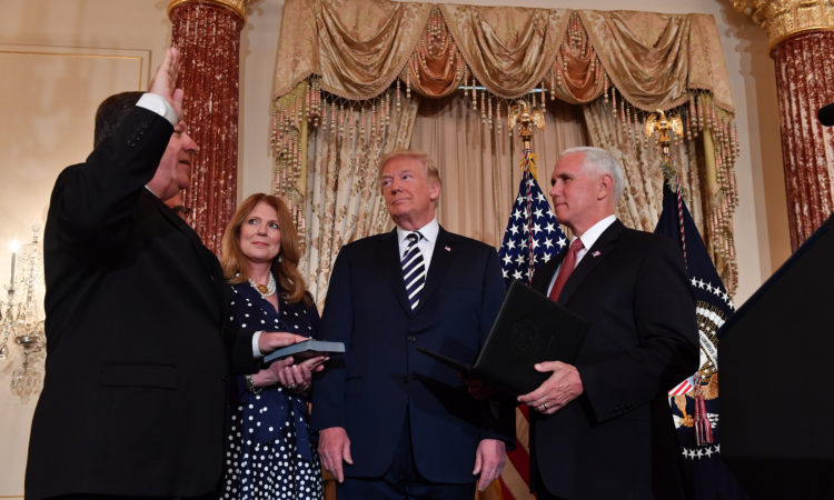 U.S. Secretary of State Mike Pompeo, flanked by Susan Pompeo and President Donald Trump, is sworn-in by Vice President Mike Pence at the U.S. Department of State in Washington, D.C., on May 2, 2018. [State Department photo/ Public Domain]