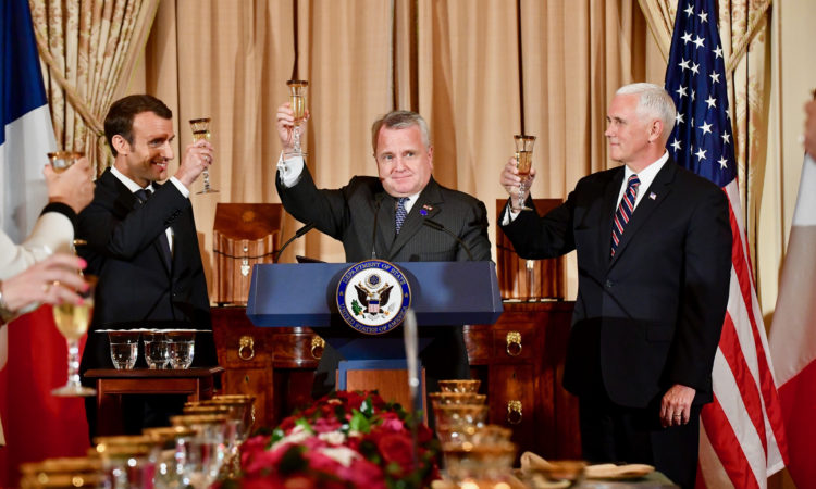 Acting Secretary of State John Sullivan flanked by Vice President Mike Pence and French President Emmanuel Macron toasts the U.S.- France relationship during the state luncheon at the U.S. Department of State in Washington, D.C. on April 24, 2018. France is a Permanent Observer at the Organization of American States. [State Department photo/ Public Domain]
