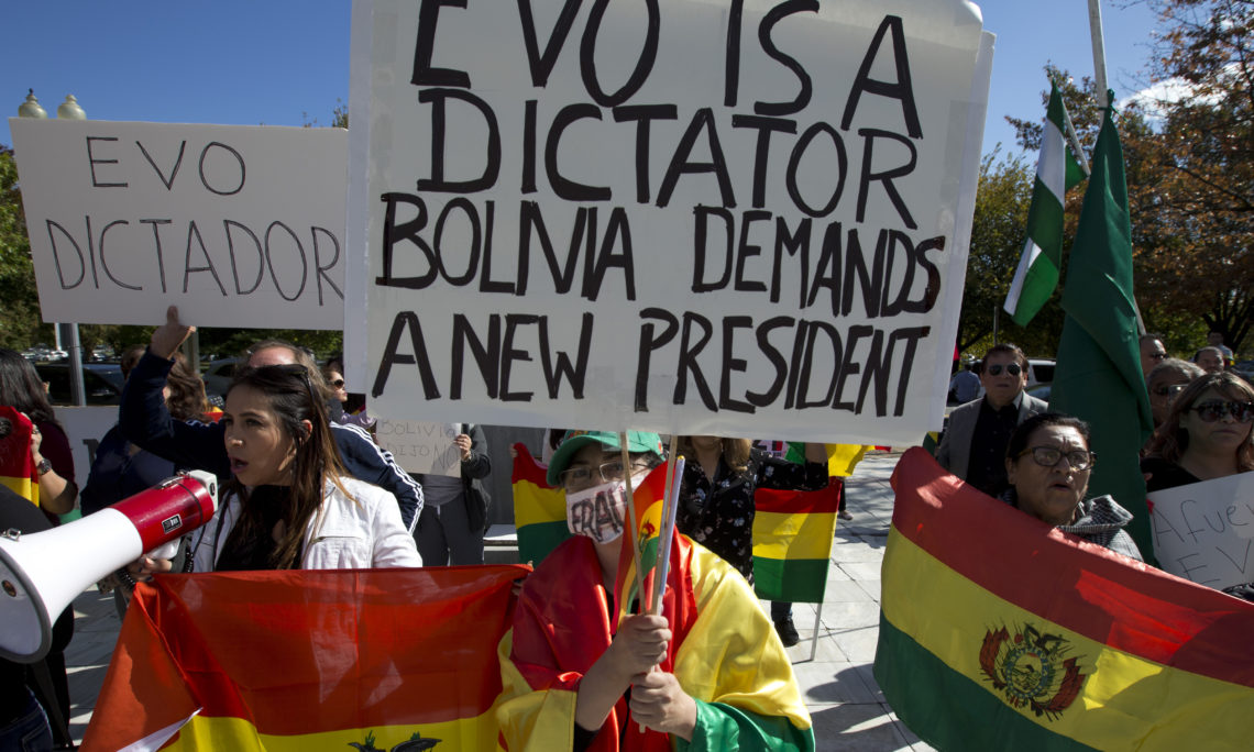 Demonstrators holding up Bolivian flags protest against the Bolivian elections outside of the Organization of American States (OAS) during a special meeting of the Permanent Council at OAS headquarters in Washington, Wednesday, Oct. 23, 2019. (AP Photo/Jose Luis Magana)