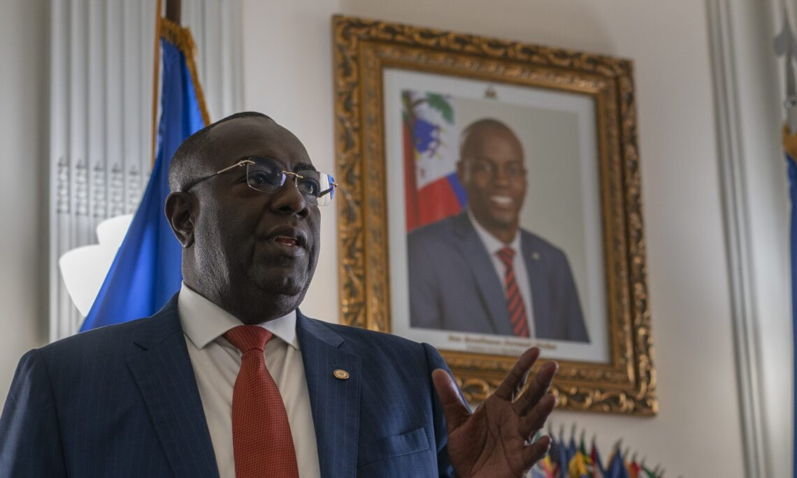 Ambassador Bocchit Edmond speaks of the late Haitian President Jovenel Moïse, during an interview with the Associated Press. A portrait of slain President Moise is seen on the wall behind, July 7, 2021. (AP Photo)