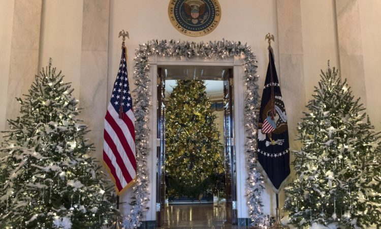 "On the State Floor of the White House, the Grand Foyer and Cross Hall celebrate the first themed White House Christmas, which was the ""Nutcracker Suite"" in 1961. The Blue Room holds the official White House Christmas tree, which is decorated with glass ornaments depicting the seal of each State and territory. (AP Photo/Carolyn Kaster)"