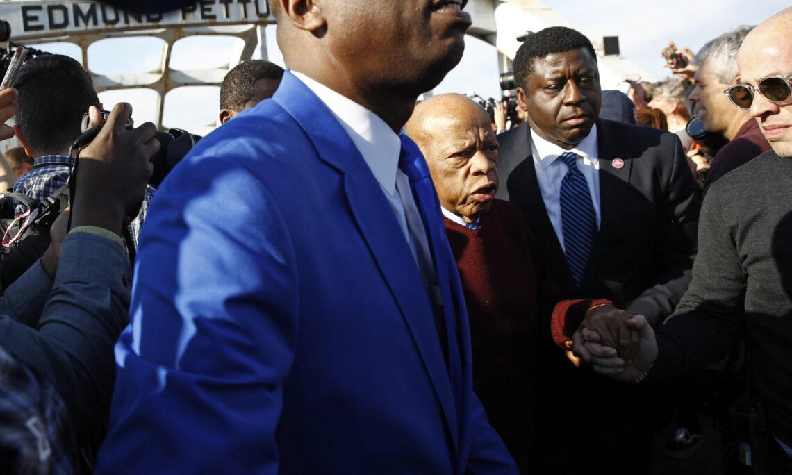 """Congressman John Lewis, leads a march across the Edmund Pettus Bridge in Selma, Alabama., Sunday, March 1, 2020, commemorating the 55th anniversary of """"Bloody Sunday."""" (AP Photo)"""