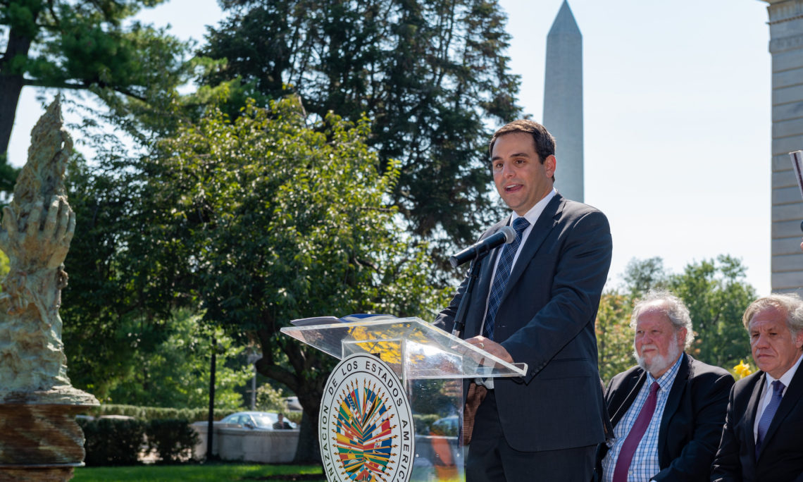 """Ambassador Carlos Trujillo, Permanent Representative of the United States to the OAS, addresses the gathering at the unveiling of the """"Tall Torch of Liberty"""" sculpture at OAS headquarters in Washington, D.C. He is joined by OAS Secretary General Luis Almagro and renowned American sculptor Greg Wyatt who donated the piece to the OAS for permanent display, September 4, 2019. (OAS Photo)"""