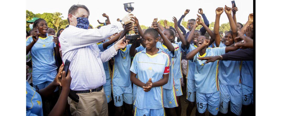 L'Ambassadeur Hankins soulève le trophée de football avec l'équipe féminine