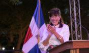 Una mujer sonrie y aplaude. Detras de ella, la bandera dominicana.