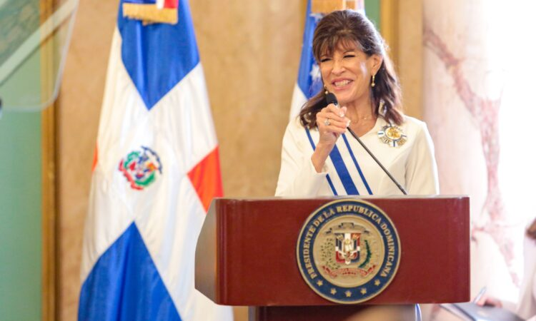 A woman smiling behind a podium, with two flags behind her.