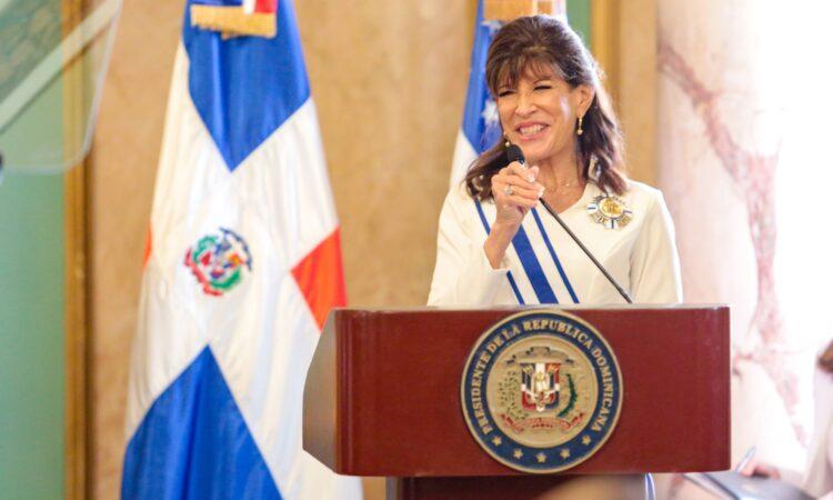 Una mujer sonriente detrás de un podio, con dos banderas detrás de ella.