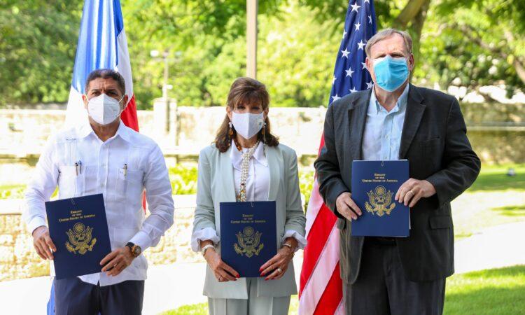 Tres personas de pie, sosteniendo carpetas con el logo y el nombre del Departamento de Estado de los Estados Unidos. Detrás de ellos, las banderas de los Estados Unidos y la República Dominicana. En los exremos hay dos hombres y en el centro una mujer.