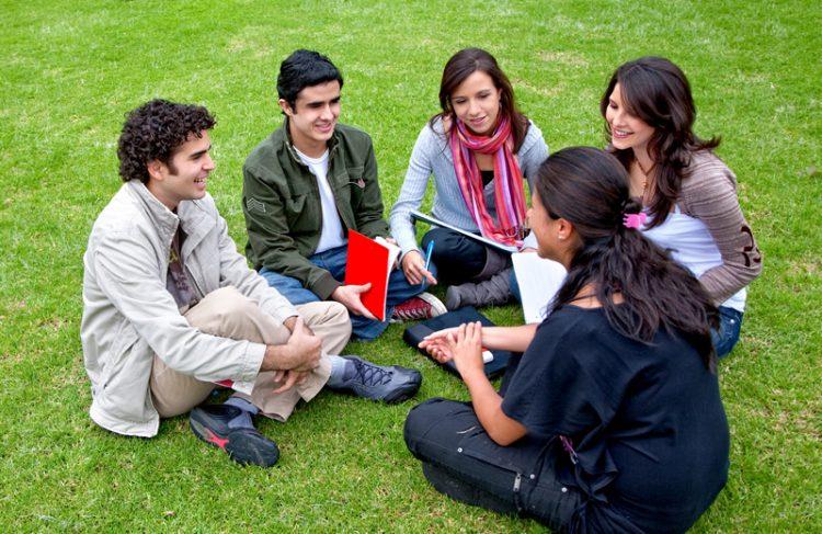 Grupo de estudiantes estudiando en un círculo.