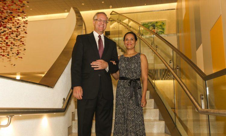 Un hombre y una mujer sonriendo frente a una escalera.