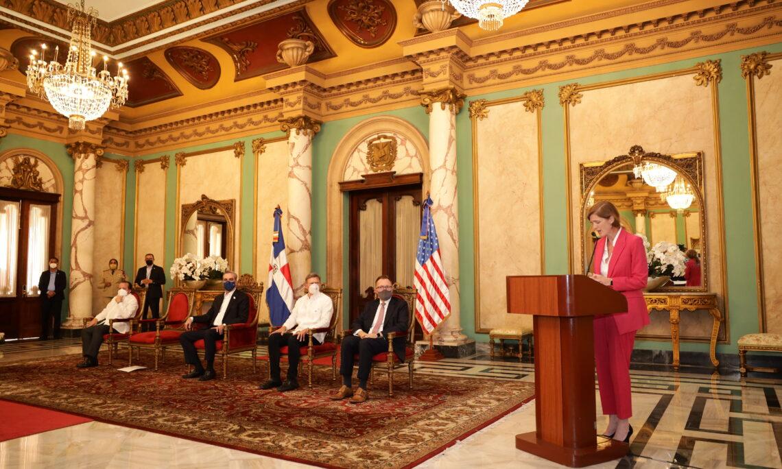 Una mujer habla desde un podio y cuatro hombres sentados escuchan, con las banderas dominicana y estadounidense detrás de ellos.