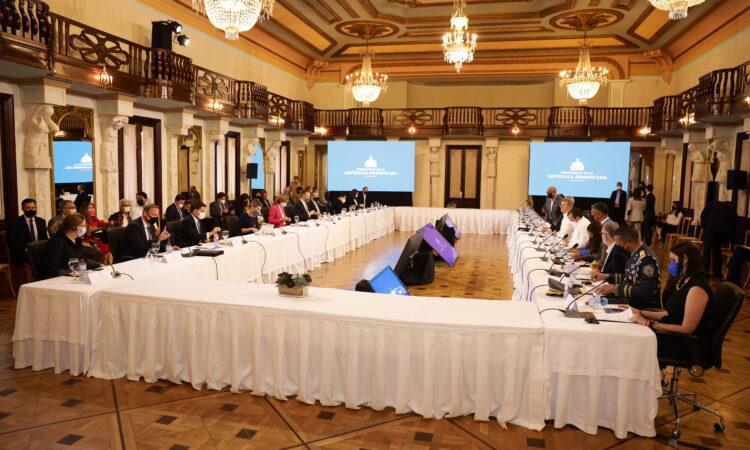 Dos filas de personas sentadas frente a frente en mesas largas, con pantallas en el fondo.