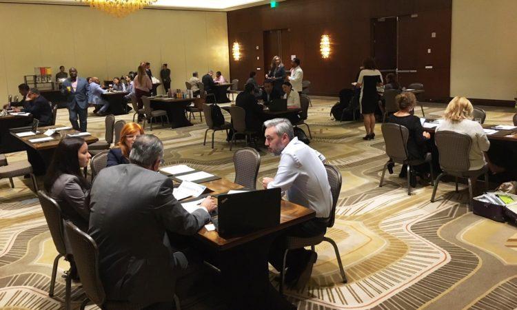 Un grupo de personas conversando en un salón de un hotel.