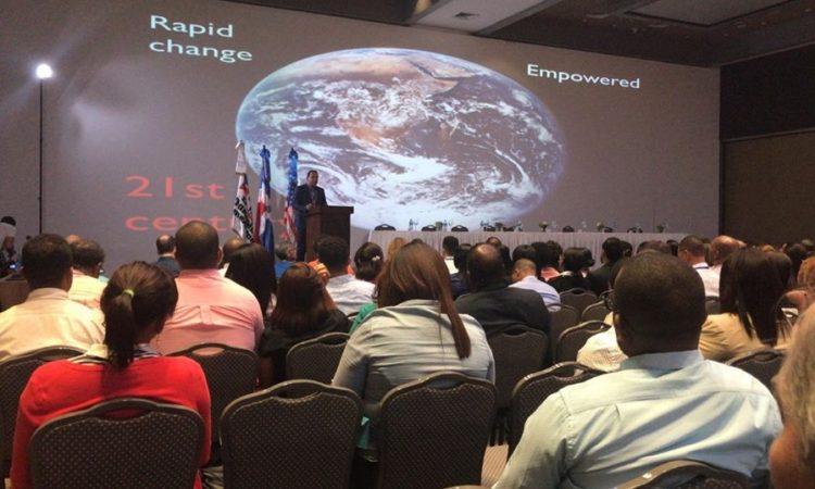 Un grupo de personas observando a un orador. Detrás del orador, una pantalla con una imagen del planeta tierra.