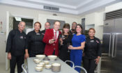 Un grupo de personas en una cocina, sonriendo, algunos de ellos con copas en la mano.