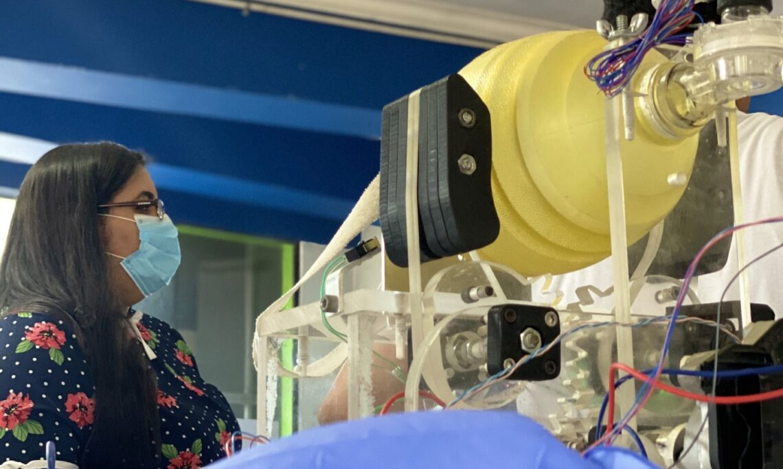 A woman wearing a mask looks at medical equipment.