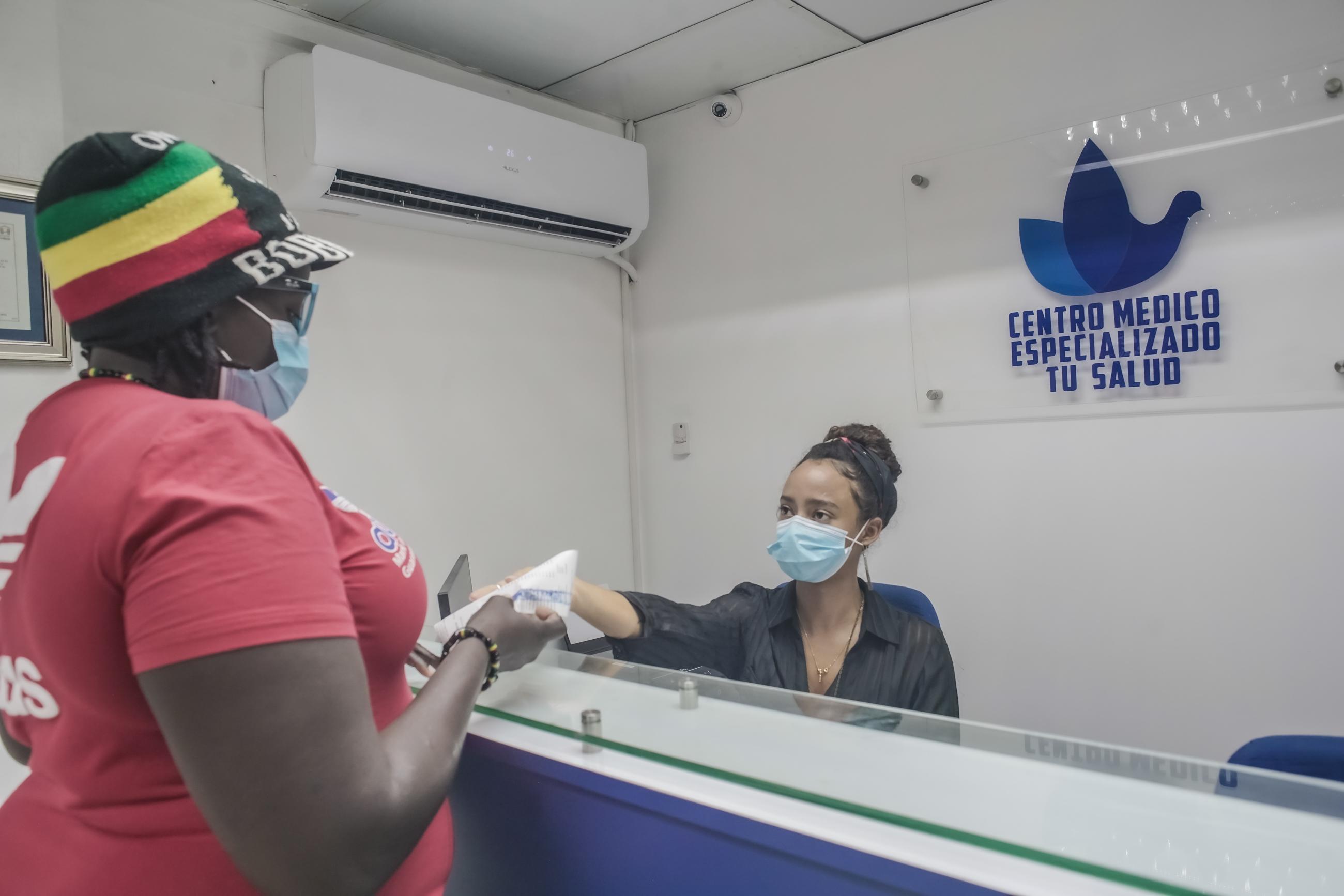 Una joven recibiendo a una señora en el centro Tu Salud
