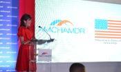 Una mujer habla y sonríe detrás de un podio. A su lado, los logos de AmchamDR y la Embajada de los Estados Unidos en Santo Domingo