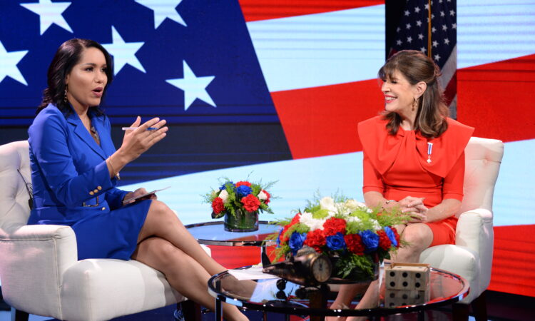 A woman speaking while another one looks at her and smiles. Behind them, the U.S. flag on two screens.