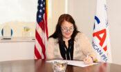 directora USAID firmando acuerdo sobre mesa y banderas de USA y USAID detrás